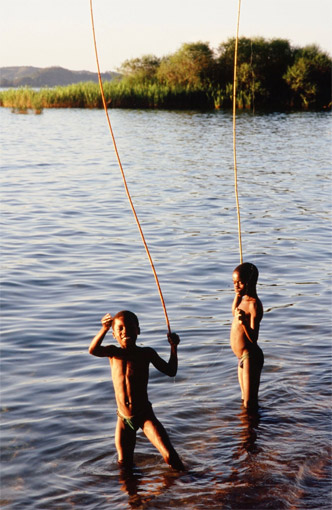 Local children bathing the late afternoon sun near reeds in Lago Niassa, Mozambique: this is peak transmission time for schistosomiasis and an ideal habitat for water snails.