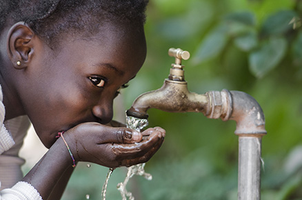African child drinking from a tap: this may or may not be safe